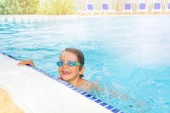 Portrait of funny boy wearing goggles swimming in the outdoor pool at sunny day