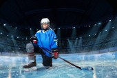 Portrét mladé hokejista s holí stojící na jednom koleni na kluzišti