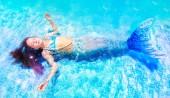 Nad zobrazením krásné dívky ve vílu plovoucí v bazénu se oči zavřené