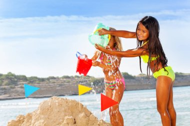 Portrait of two girls in bikini splashing water from toy buckets, spending summertime on the beach