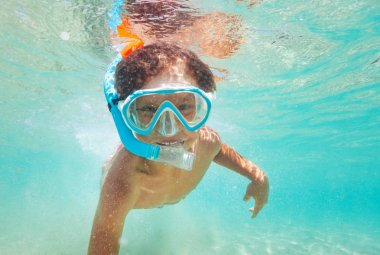 Close up portrait of kid boy snorkeling in clear blue sea during summer vacation