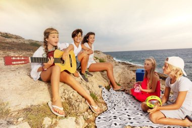 Group of teenage friends, happy musicians, singing and playing musical instruments while relaxing on the beach in summer camp