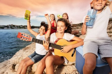 Portrait of excited teens having picnic outdoors, playing guitar and drinking beverages at the seaside