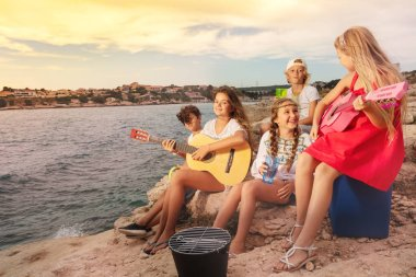 Portrait of teenagers, happy friends, having picnic and playing guitar outdoor on the beach