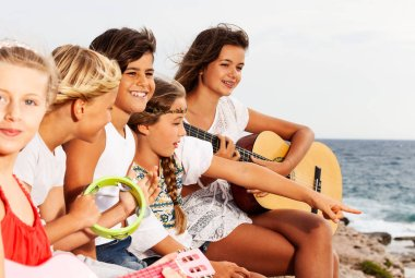 Group of teenagers, young music band, playing guitar and singing songs at the seaside in summer camp