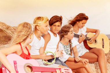 Portrait of teenage boys and girls, sitting on the beach, playing guitar during sunset