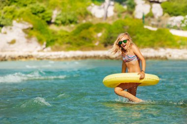 Portrait of beautiful teenage girl in sunglasses running into the sea with yellow swimming ring