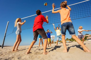 Back view of teenage boys hitting the ball during volleyball competition on the beach in summer
