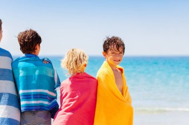 Portrait of happy teenage boy wrapped in towel drying off on the beach with his friends
