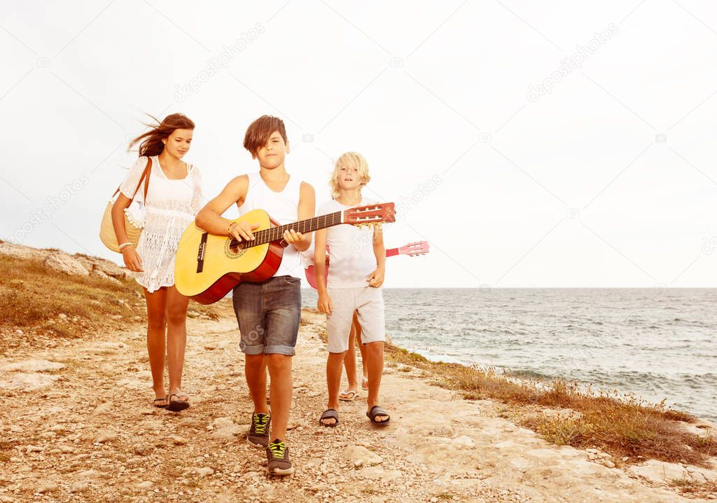 Teenage boy walking on the beach with friends and playing guitar