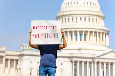 Man protest in front of the USA capitol in Washington holding sign sayin  illegitimate president