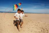 Dva kluci bratři na písečné pláži běh s barevnými svlečené duha barvy draka v ležérní letní oblečení