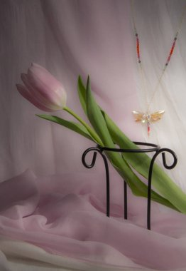 Pink tulip on stand with dragonfly golden sparkle necklace on soft pink background