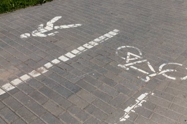 part of the sidewalk road divided by symbols halfway for pedestrians and cyclists