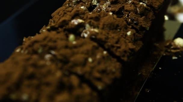 Closeup panorama na řezané chutný čokoládový dezert zdobený drcené arašídy a čokoládový prášek