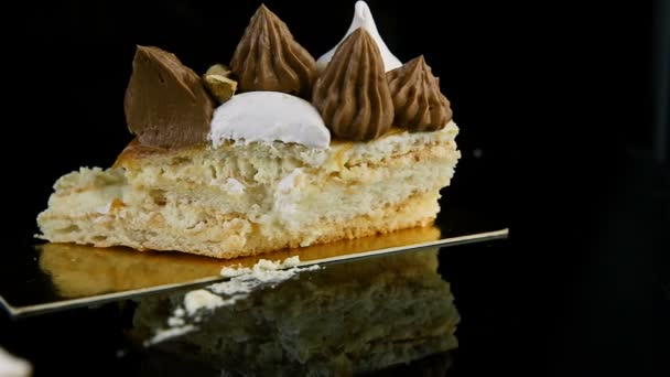 broušená část lahodné dvouvrstvé Kyjev dort hojně zdobena čokoládový krém a ořechy stojí na pozadí černé zrcadlo s odrazem