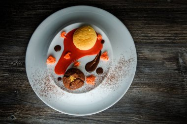top view of delicious dessert of round small cake and chocolate truffle with red vanilla sauce decoration on white plate