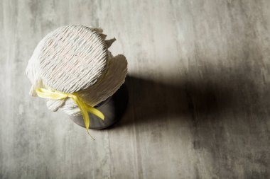 top view of small jar covered with handmade tissue and yellow ribbon stand on grey table