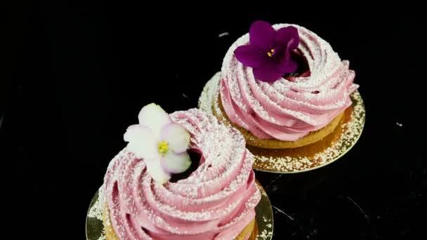 plynulé panorama dolů na dva soubory cookie růžové zephyr zdobené fialové a bílé květy na černé