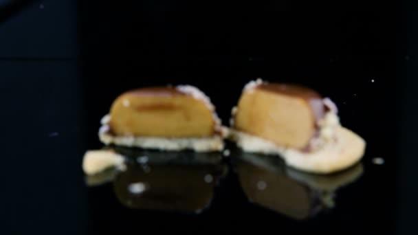 Vergrößern Sie in Scheiben geschnitten auf der Hälfte Französisch Mini-Mousse-Gebäck Dessert mit Schokolade Glasur bedeckt und mit zerkleinerten Nüssen auf schwarzem Spiegelhintergrund dekoriert