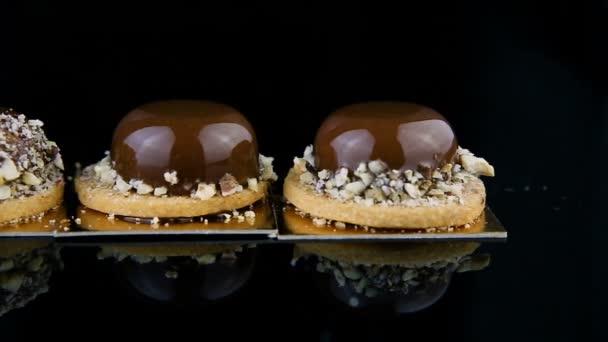 Panorama ze tří francouzské pečivo zákusky mini kolo pěna potažen čokoládovou polevou a zdobí drcenými ořechy podávané na pozadí černé zrcadlo