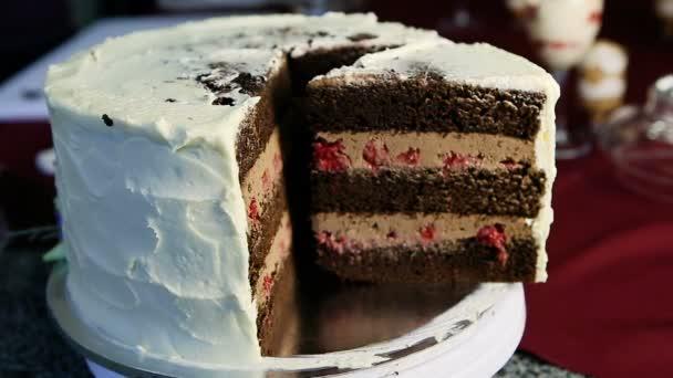 Nahaufnahme in Scheiben geschnitten großen Schokoladenkuchen mit Karamell und Kirschfüllung mit weißer Sahne dekoriert