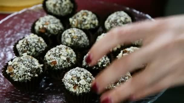 Closeup cukrovinky ruce dát čokoládové bonbóny zdobené s drcenými ořechy podávané na kruhové desky