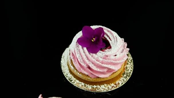Closeup ruku dá jeden růžový ibišek cookies s fialovými a bílými květy malé sadě na černém pozadí