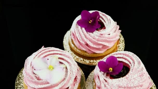 closeup panorama down on three pink zephyr cookies decorated with violet and white flowers served on black