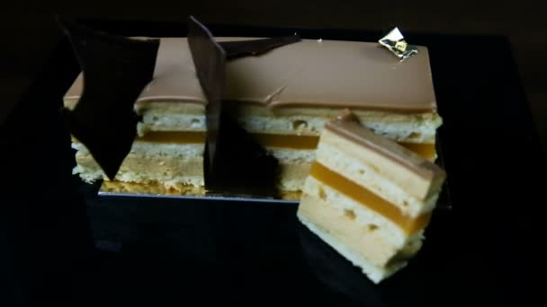 Fokussieren Sie sich auf ein aufgeschnittenes Stück mehrschichtigen Karamellkuchens mit Gelee-Füllung verziert mit Schokolade auf schwarzem Hintergrund serviert