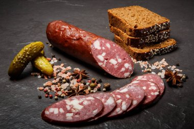 Delicatessen dry salami sausage with sliced pieces served with pink salt, spices, rye bread slices, and pickled cucumbers stock vector