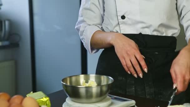 detailní ženské ruce krájené nožem čerstvé máslo do kovové mísy na elektronických váhách