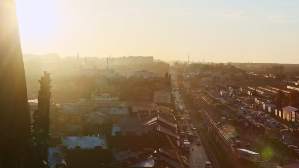 top view of long street with many cars passing by in old histirical town Lviv on sunset against clear golden sky