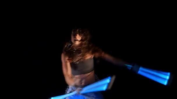 schöne Zigeunerin tanzt in Neonlicht mit ultravioletten Stäben