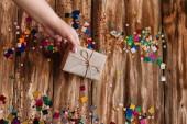 ženská ruka dát zabalený dárek na dřevěný stůl, kde je rozptýlené konfety