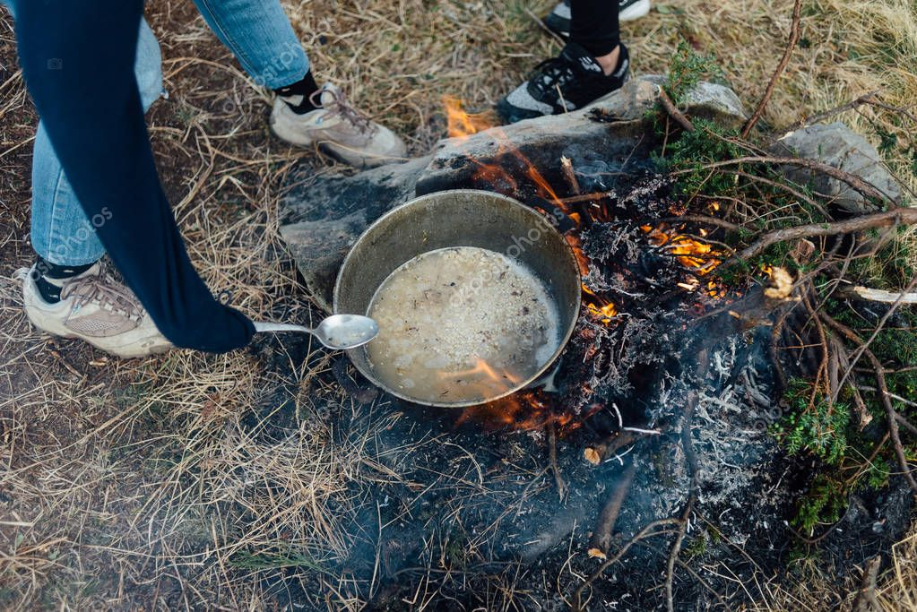 Cooking on a campfire during a hiking trip.