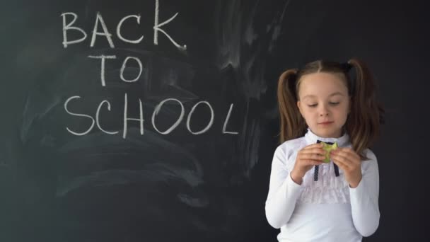 A hungry schoolgirl stands near the blackboard. She is eating a green apple. Change at school. Training. Education. Children.