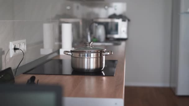 Kitchen video. Boiling pots on the stove. White steam from hot water. Cooking process.