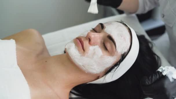 Kosmetička aplikující enzymatický peeling na ženskou tvář v lázních. Použije bílou masku se štětcem. Kosmetický zákrok v moderním salónu krásy