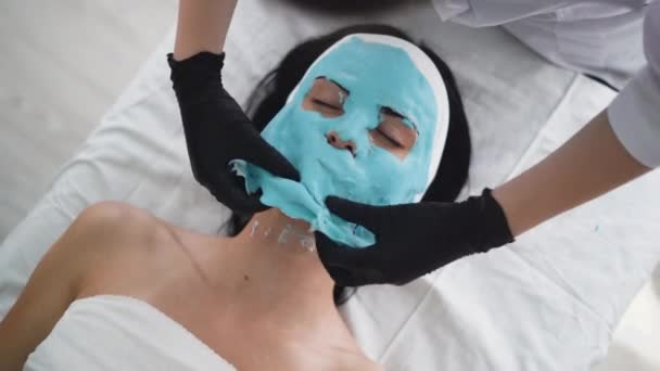 Krásná mladá žena na recepci v kosmetik, alginát maska, proces odstraňování horní pohled. Zblízka. Kosmetický zákrok v moderním salónu krásy.
