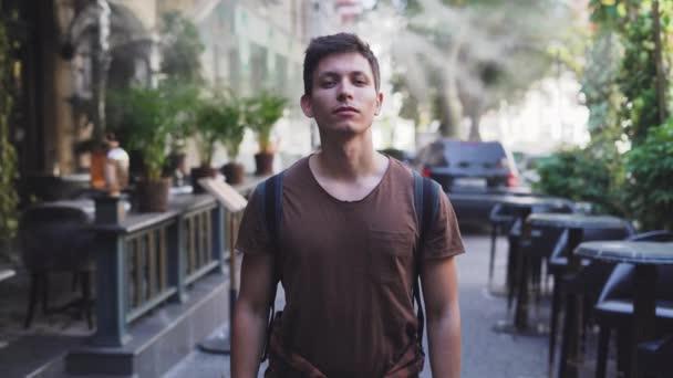 fiatal kaukázusi férfi turista az utcán meleg időben. Köd, vízcseppek hűvösek. Kiváló minőségű 4k felvételek