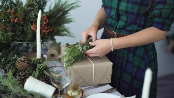 holidays, new year and christmas concept - close-up of female hands decorate a box with a gift