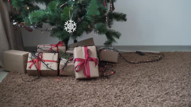 close-up of santa claus hand, goes to the tree and picks up a gift