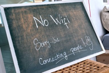 No Wi Fi sign. Sorry, but connecting people - chalk text written on blackboard at restaurant. Talk to each other concept