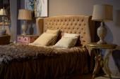 Luxus és gazdag szállodai szoba. Elbűvölő és elegáns barokk álom hálószoba design belső. Barna, bézs színű, senki sem. Ágytakaró és a párnák az ágyon. Gazdag retro vintage stílusú. Éjjeli lámpa