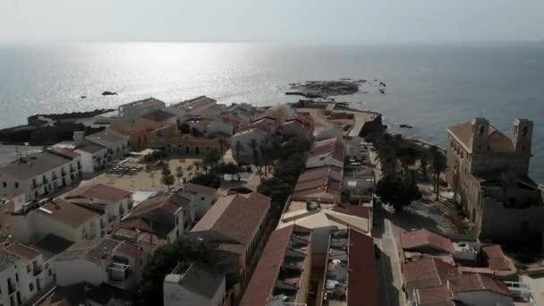 Aerial panoramic view townscape and old church of St Peter and St Paul of Tabarca Island at summer. Roofs of coastal residential houses, tranquil Mediterranean Sea, rocky coast. Spain
