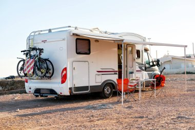 Empty folding chairs and table under canopy near recreational vehicle camper trailer. Adventure journey, active people traveling by motor home concept