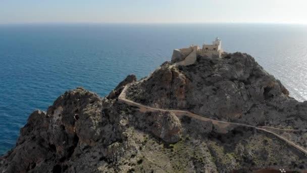 Video vom Standpunkt der Drohne mesa roldan Leuchtturm auf der Klippe, blaues ruhiges Mittelmeer im Naturpark cabo de gata-nijar, Provinz Almeria, Andalusien. Spanien
