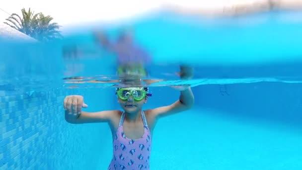 Zeitlupe Ansicht kleine 7-8 Jahre alte Mädchen tragen Badeanzug und Brille in Wasser getaucht genießen Sommerferien Schwimmen im Pool. Aktiver Lebensstil und sportliches Aktivitätskonzept