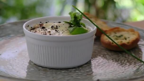 Zblízka v bílé míse houba julienne na talíři točí kolem. Zpomalený pohled. Jídelní lístek restaurace, žádní lidé